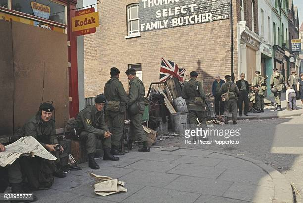 View of British Army soldiers patrolling and resting in front of boarded up shops and a barricade of refuse bins debris and barbed wire lined across...