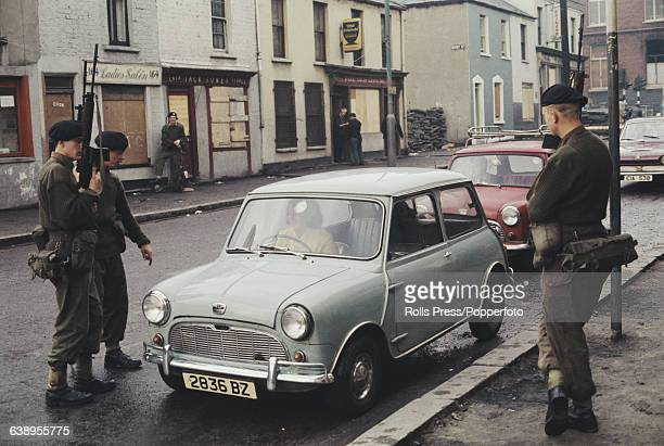 View of British Army soldiers patrolling and stopping cars to carry out security checks at a temporary roadblock on a street in Belfast Northern...