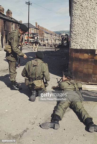 View of British Army soldiers patrolling in front of a barricade of burnt out buses and barbed wire on a residential street in Belfast Northern...