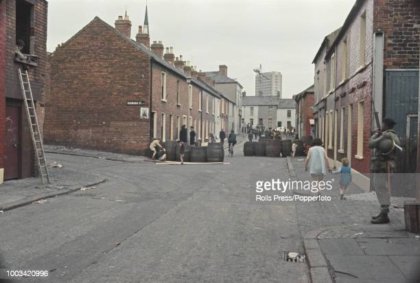 View of British Army troops standing guard near a barricade of oak barrels on a residential side street next to a barbed wire barricade in the...