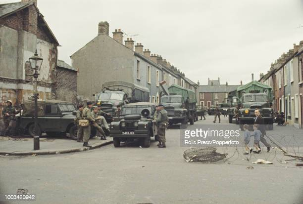 View of British Army troops standing next to army Land Rovers and trucks on a residential side street next to a barbed wire barricade in the...