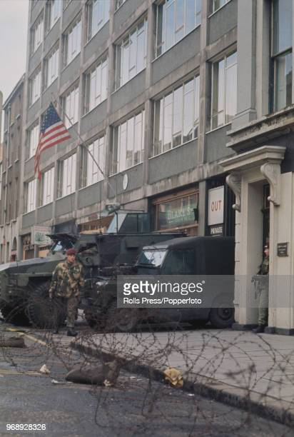View of British Army troops with a Humber Pig and Land Rover positioned on guard outside the United States Consulate building in Belfast, Northern...