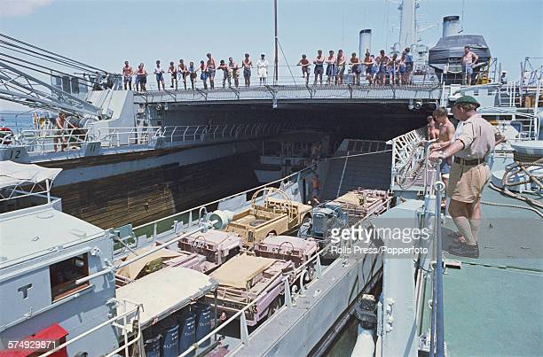 View of British Army vehicles tied to a landing craft being loaded on to the Royal Navy ship HMS Fearless during a planned withdrawal of troops and...