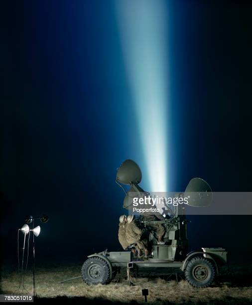 View of British Auxiliary Territorial Service searchlights of AntiAircraft Command on the Home Front illuminating the night sky during World War Two...