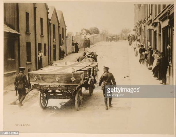View of British flagcovered coffins of victims of the RMS Lusitania are carried on a horsedrawn wagon to a temporary morgue Queenstown Ireland May...
