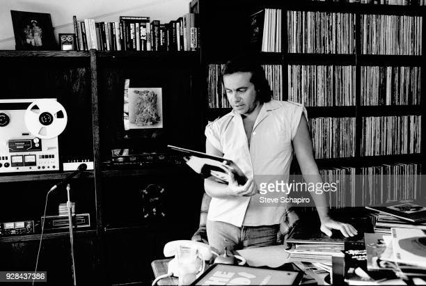 View of British musician and lyricist Bernie Taupin as he looks at a record in his home office Los Angeles California April 1980