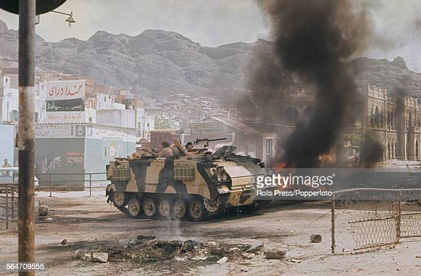 View of British troops in a FV432 armoured personnel carrier on patrol driving past burning debris on the streets of Aden town following a period of...