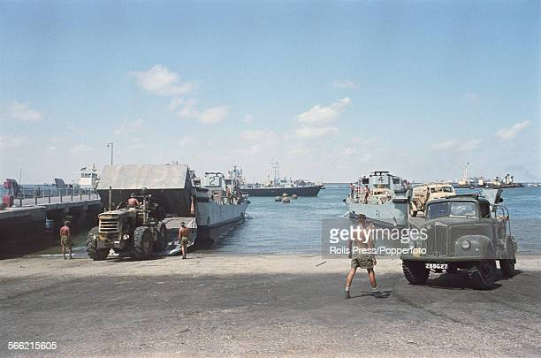 View of British troops loading vehicles and equipment on to landing craft in Aden harbour during a planned withdrawal from Aden and Yemen on 5th...