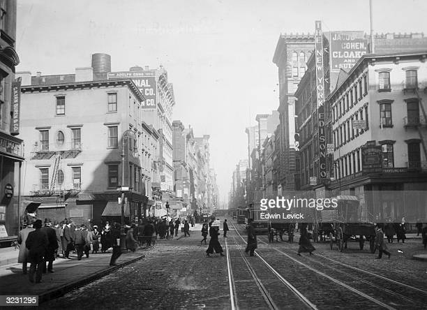 View of Broadway, looking north from Canal Street, New York City. Street cars and horse-drawn carriages provide transportation.