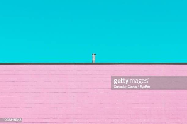 view of building wall against blue sky - pink tube photos et images de collection