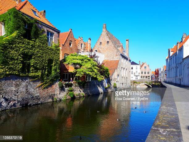 view of buildings against blue sky, reflected in canal water, in bruges - moat stock pictures, royalty-free photos & images