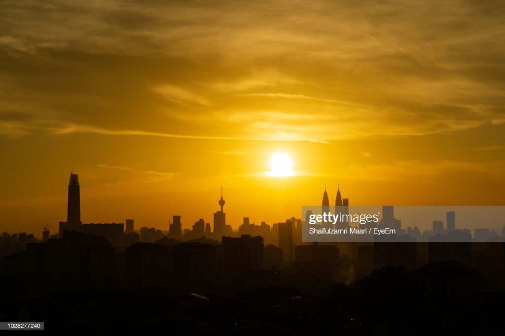 View Of Buildings Against Cloudy Sky During Sunset : Stock Photo