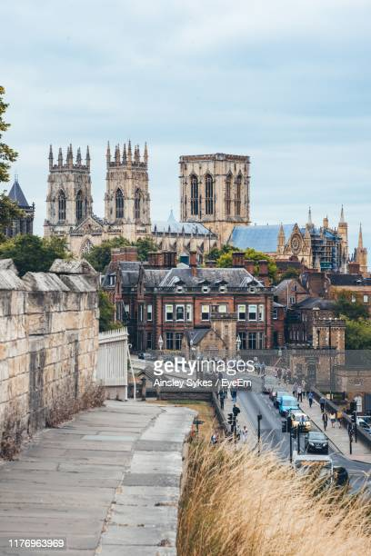 view of buildings against cloudy sky - york minster stock pictures, royalty-free photos & images