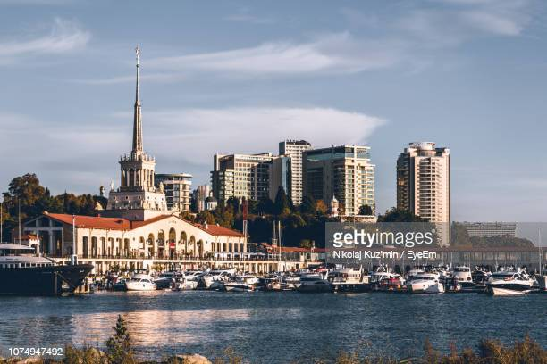 view of buildings at waterfront against cloudy sky - sochi stock pictures, royalty-free photos & images