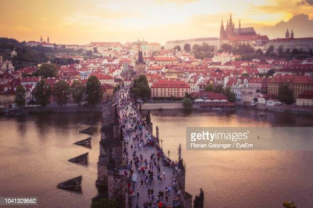 view of buildings at waterfront during sunset - prag stock-fotos und bilder