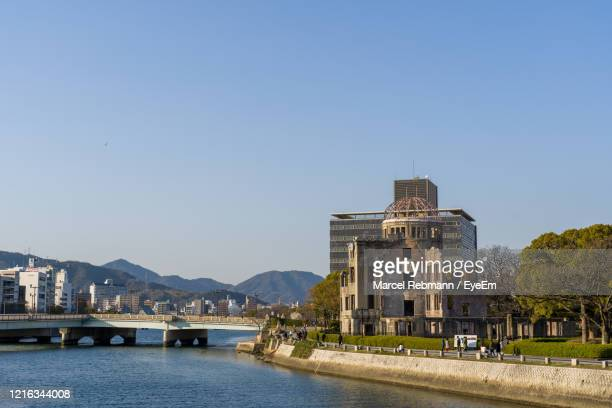 view of buildings by river against clear blue sky - atomic bombing of hiroshima stock pictures, royalty-free photos & images