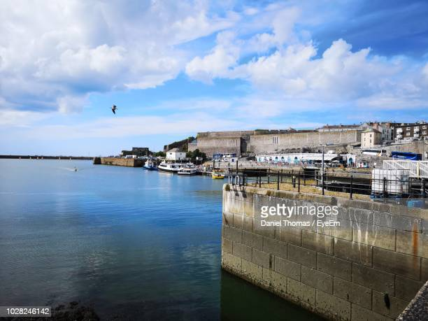 view of buildings by river against cloudy sky - plymouth stock photos and pictures