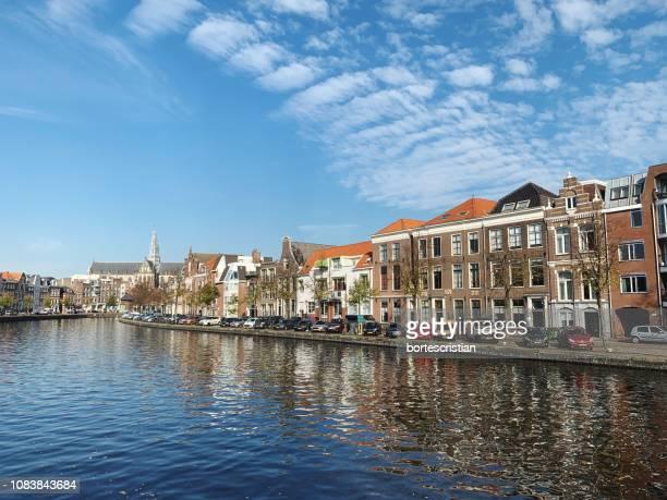 view of buildings by river against cloudy sky - bortes stockfoto's en -beelden