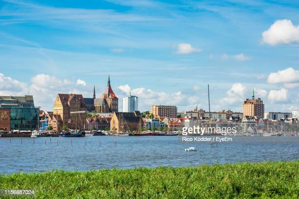 view of buildings by river against cloudy sky - rostock stock pictures, royalty-free photos & images
