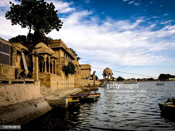 view of buildings by river against cloudy sky - udaipur stock pictures, royalty-free photos & images
