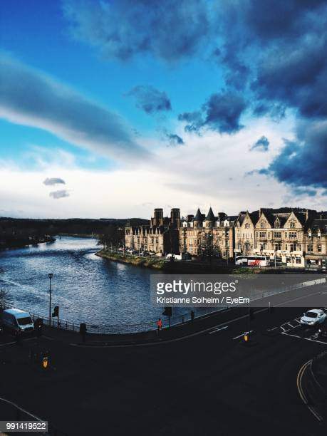 view of buildings by river against cloudy sky - inverness scotland stock pictures, royalty-free photos & images