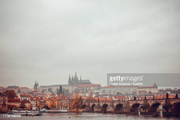 view of buildings by river against sky in city - fedor stock pictures, royalty-free photos & images