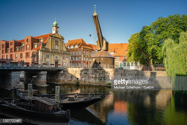 view of buildings by river against sky - lüneburg stock pictures, royalty-free photos & images