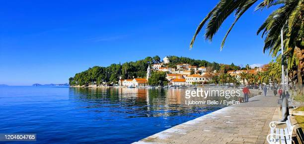 view of buildings by sea against blue sky - ljubomir belic stock pictures, royalty-free photos & images