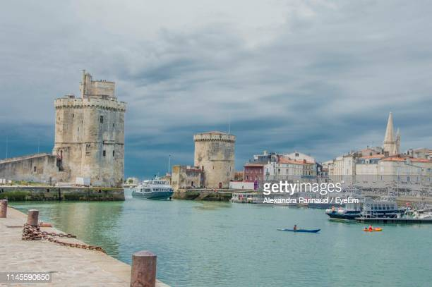 view of buildings by sea against cloudy sky - la rochelle stock pictures, royalty-free photos & images