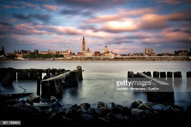 view of buildings by sea against cloudy sky - antwerpen stad stockfoto's en -beelden