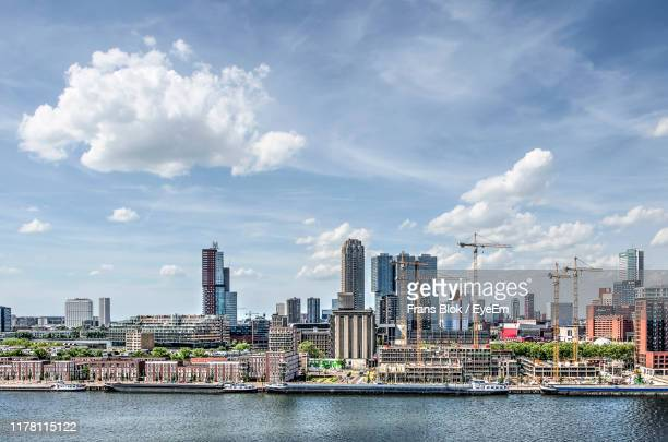 view of buildings in city against cloudy sky - hollande méridionale photos et images de collection