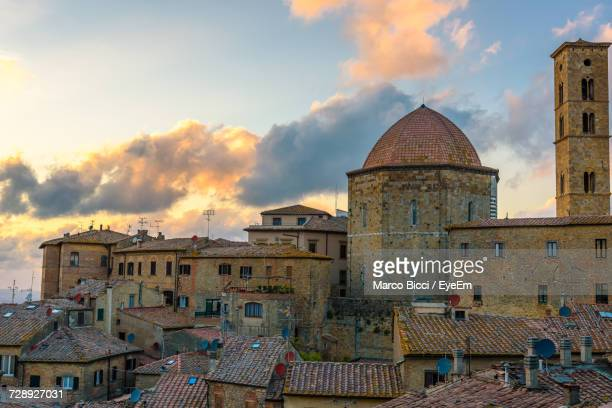 view of buildings in city against cloudy sky - volterra stock photos and pictures