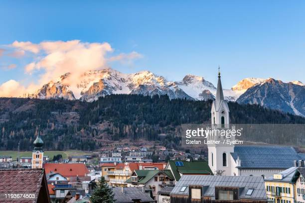 view of buildings in town against cloudy sky - schladming stock pictures, royalty-free photos & images