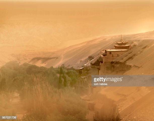 View of buildings, including entrance to the Mogao Caves , and the landscape beyond, obscured by a dust storm, Dunhuang, Gansu province, China, April...