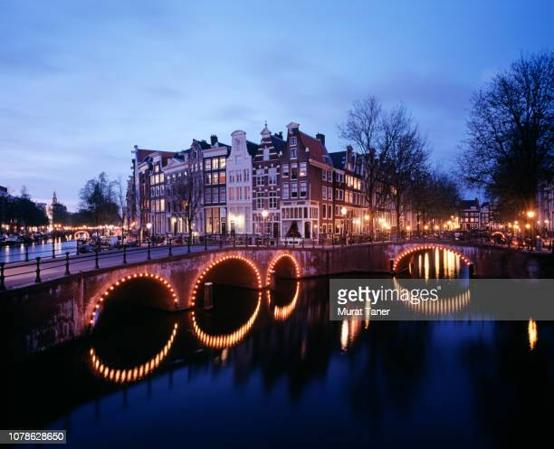 view of buildings on the canal in amsterdam - ponte ad arco foto e immagini stock