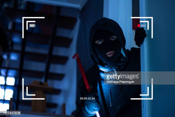 cctv view of burglar breaking in to home through window with crowbar - burglary stock pictures, royalty-free photos & images