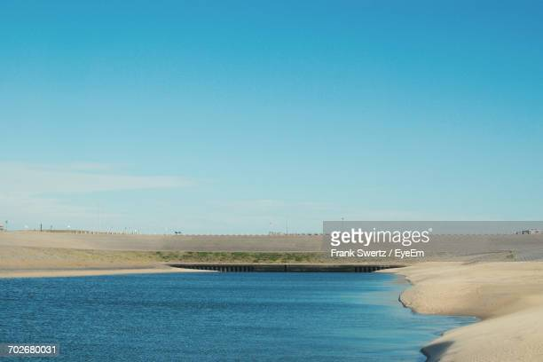 view of calm beach against blue sky - frank swertz stock photos and pictures
