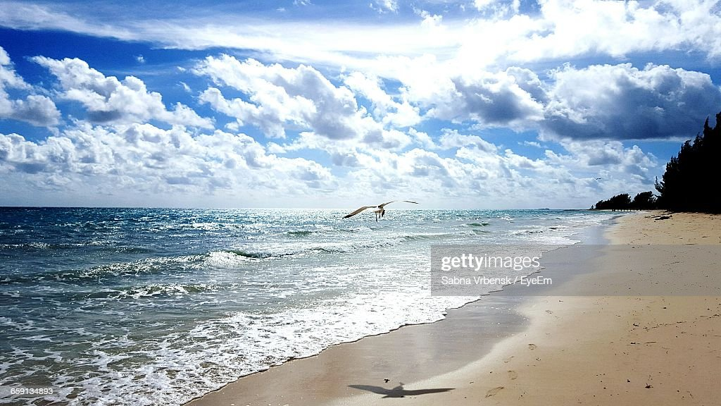 View Of Calm Beach Against Cloudy Sky : Stock Photo