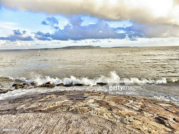 view of calm beach against the sky - llanelli stock pictures, royalty-free photos & images