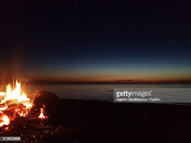 View Of Calm Beach With Bonfire In Foreground