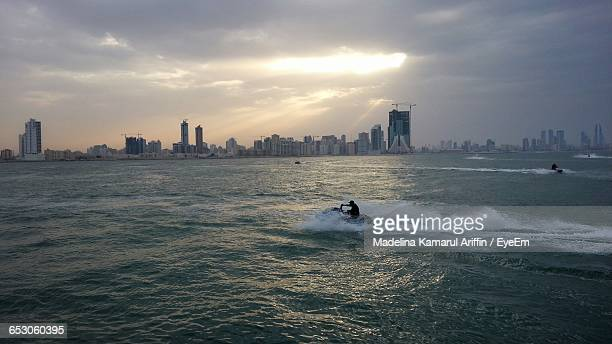 view of calm sea with cityscape in background - manama stock pictures, royalty-free photos & images
