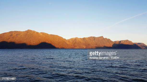 View Of Calm Sea With Mountain Range In Background