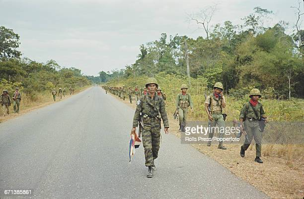 View of Cambodian government troops walking along a road to the capital city of Phnom Penh during fighting between Khmer Rouge communist fighters and...