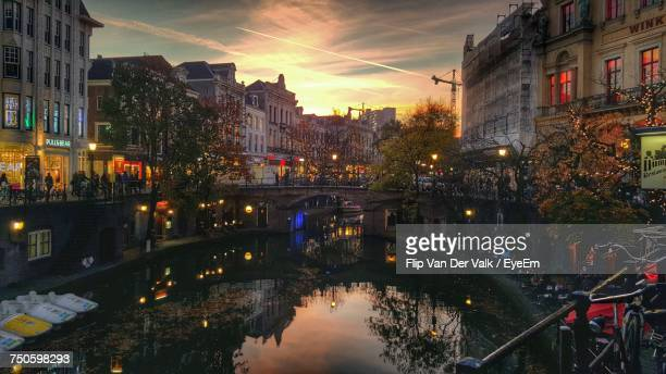 view of canal in city at dusk - utrecht stock-fotos und bilder