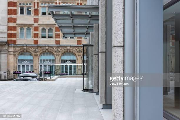 View of canopied entrance to main tower looking east to Bury Street and terracotta clad building. The Economist Building, London, United Kingdom....