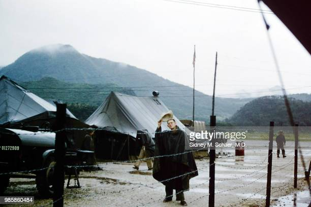 View of Captain Jim C Jones of the 8063rd MASH dressed in a poncho as he doffs a straw hat in the rain South Korea January 1952