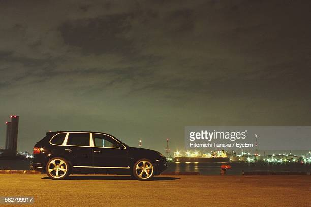 view of car by river at night with city in background - 固定された ストックフォトと画像