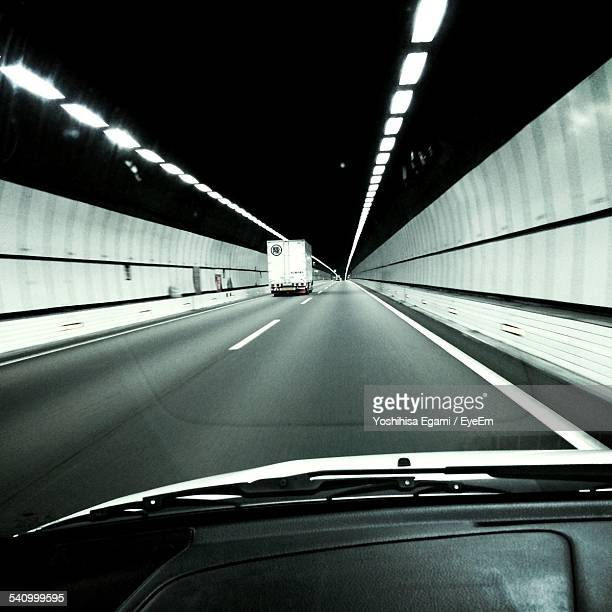 View Of Car Moving In Illuminated Tunnel Through Windshield