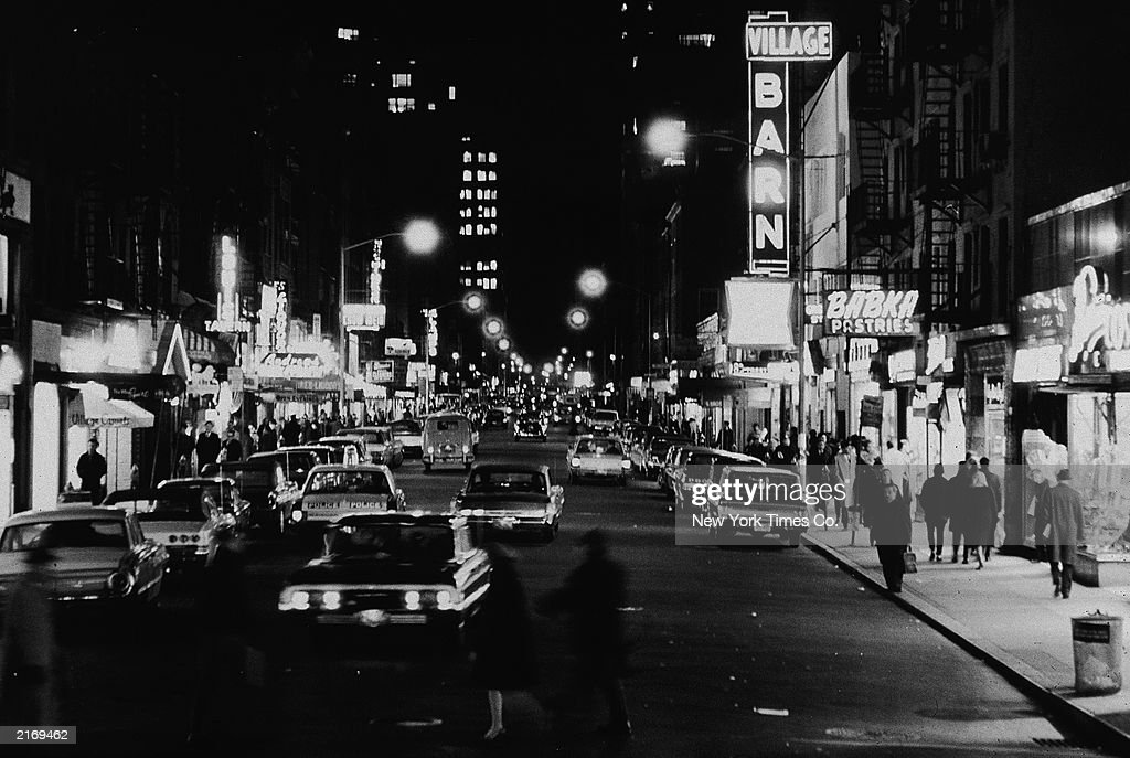 View of cars and club marquees on Eighth Street at night, looking east from Sixth Avenue in Greenwich Village, New York City, November 18, 1965.