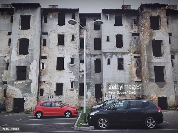 view of cars parked against abandoned building - boban stock pictures, royalty-free photos & images